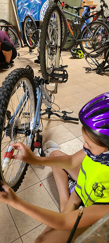 young riders prepare bikes at the Center of Southwest Culture